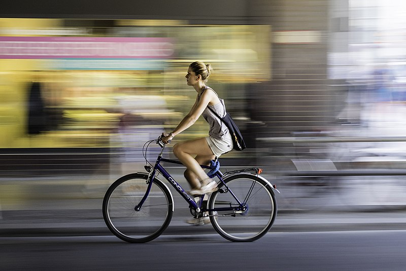Image is a photo of a woman cycling in an urban street and wearing summer clothes. The photo has been taken as she moves, with the background blurred, giving the photo an added sense of movement.